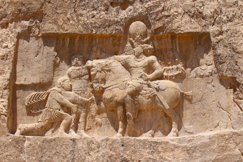 Naqsh-e Rustam, Iran Sollievo della roccia del trionfo di Sapore I sopra gli imperatori romani Valeriano e Filippo l'Arabo immagini stock