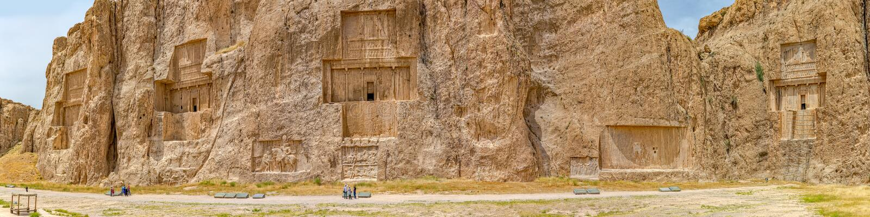 Naqsh-e Rustam Panorama. NAQSH-E RUSTAM, IRAN - MAY 3, 2015: Tourists sightseeing the historical monuments of ancient necropolis near ruins of old city stock photo