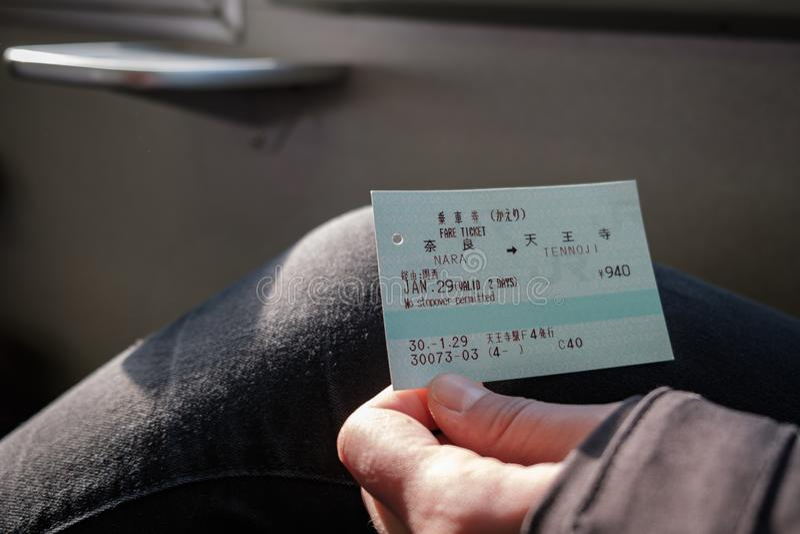 NARA, GIAPPONE - 30 GENNAIO 2018: La persona che tiene un JUNIOR recinta il biglietto di treno da Nara a Tennoji fotografie stock