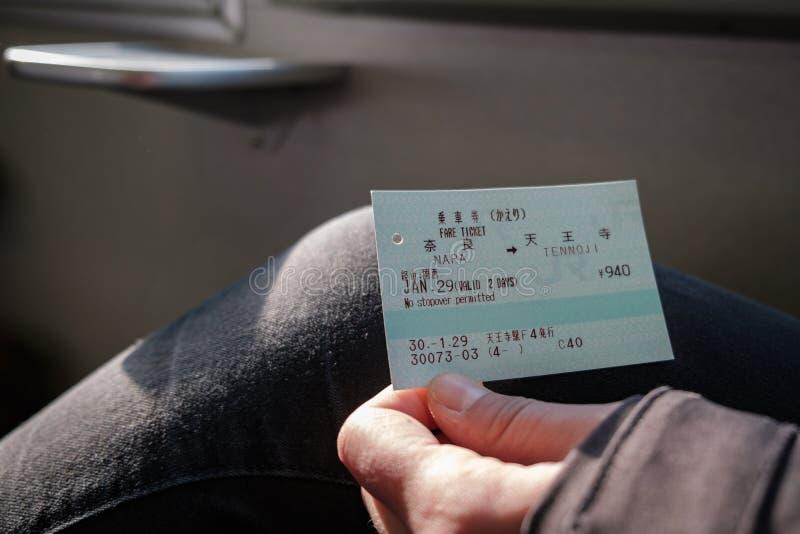 NARA JAPAN - JANUARI 30, 2018: Personen som rymmer en JR, Rails drevbiljetten från Nara till Tennoji arkivfoton