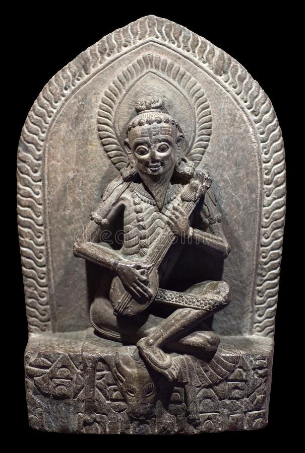 Narada - heavenly musician. Ancient Nepalese wooden statuette. P. Narada - heavenly musician. Ancient Nepalese stone carving. Nepal, 15-16th century. In Hindu stock photo