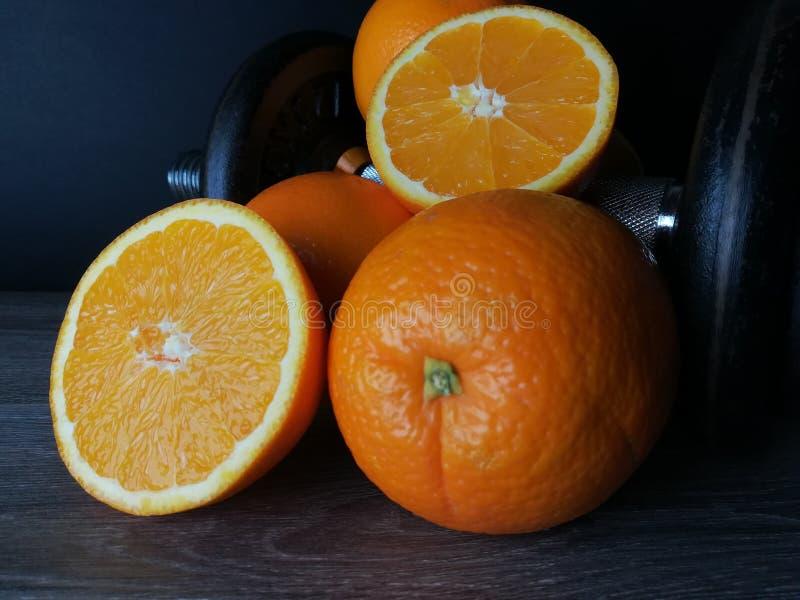 Naranja con los pesos, la salud y la aptitud imagenes de archivo