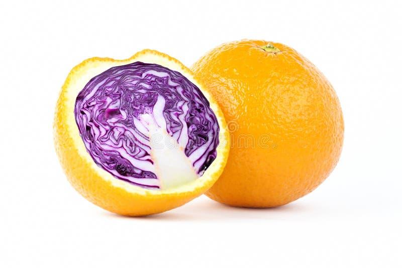 Naranja cortada con la col roja dentro de la manipulación de la foto en el fondo blanco imagenes de archivo