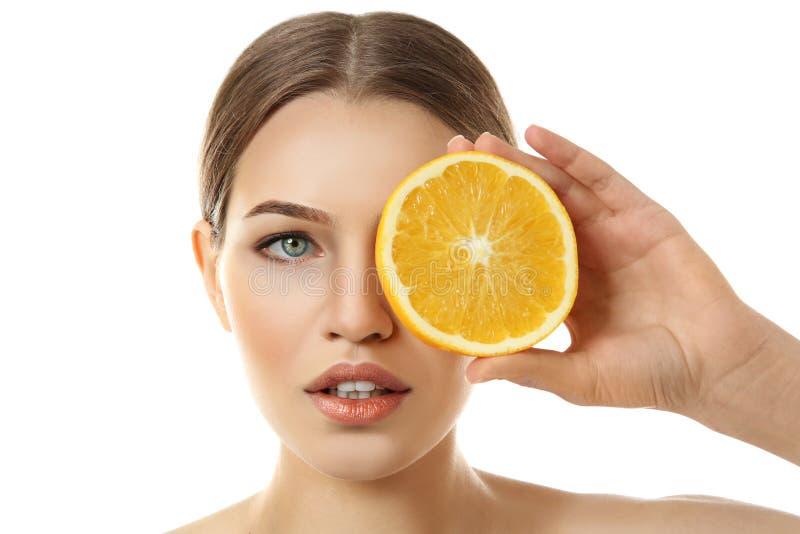 Naranja cortada tenencia hermosa de la mujer joven imagen de archivo