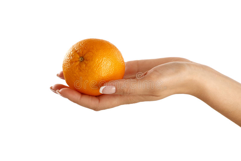 Naranja deliciosa en una mano hermosa femenina foto de archivo