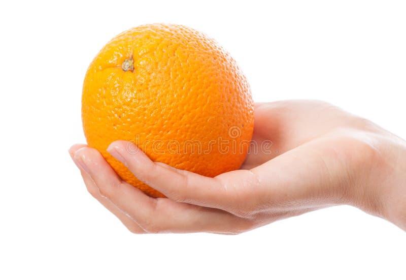 Naranja en una mano femenina imágenes de archivo libres de regalías