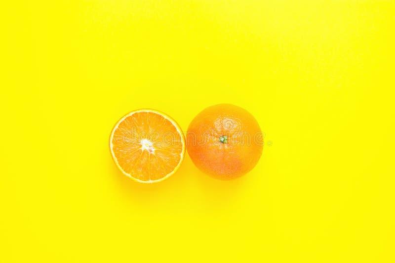 Naranja entera y partida en dos jugosa madura en fondo amarillo sólido Frutas tropicales del vegano del Detox del verano de la di foto de archivo