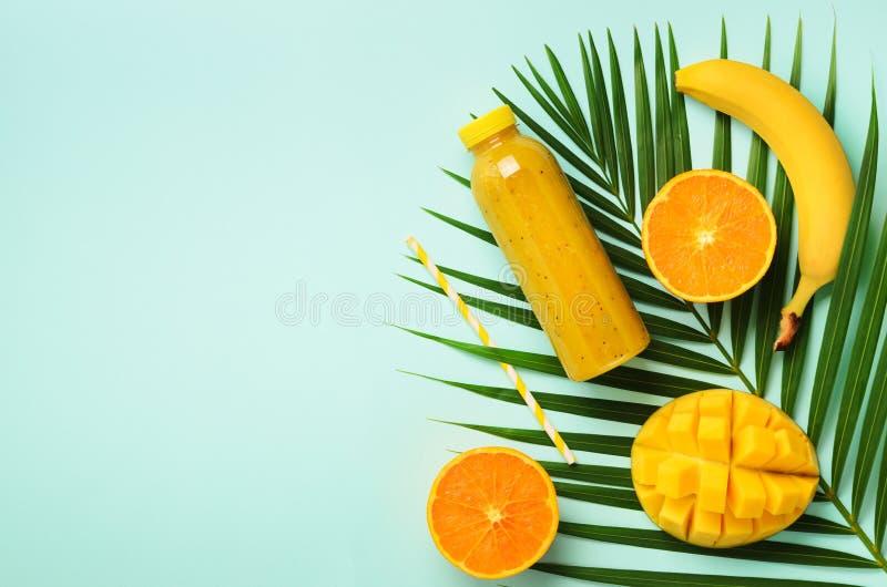 Naranja fresca, plátano, piña, smoothie del mango y frutas jugosas en hojas de palma sobre fondo azul Bebida del verano del Detox imágenes de archivo libres de regalías