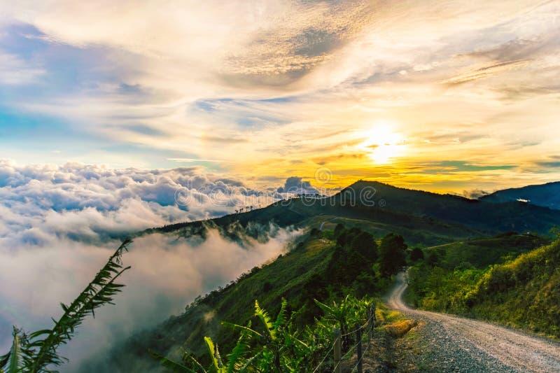 Naranja hermosa de la puesta del sol con un camino entre las montañas foto de archivo