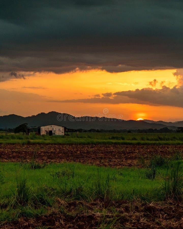 Naranja hermosa de la puesta del sol con una casa vieja y las nubes fotos de archivo