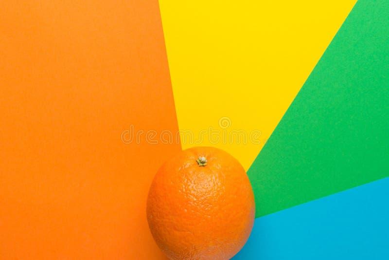 Naranja jugosa brillante madura en fondo rayado del resplandor solar del molinillo de viento multicolor del arco iris Endecha pla foto de archivo libre de regalías