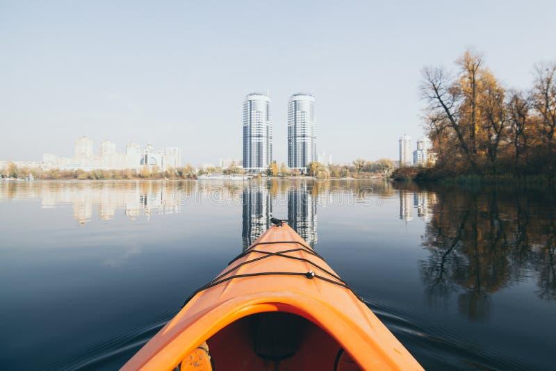 Naranja kayak navegando hacia edificios modernos en las aguas del río Dnipro en Kiev, Ucrania foto de archivo libre de regalías