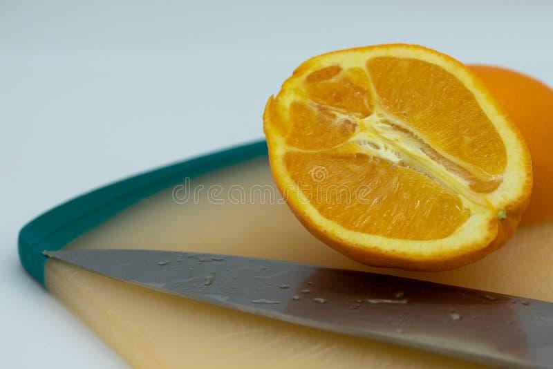 Naranja y cuchillo en tabla de cortar foto de archivo libre de regalías