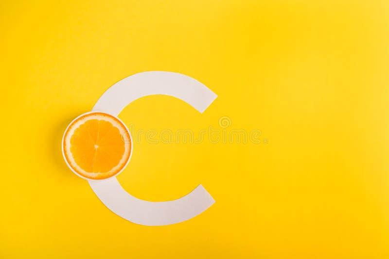 Naranja y letra C en un fondo amarillo El concepto de la vitamina S Protección del otoño contra los fríos, antioxidantes fotos de archivo libres de regalías