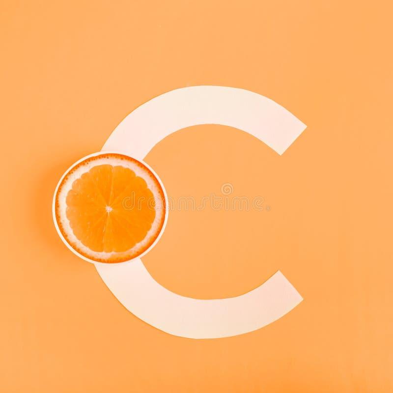Naranja y letra C en un fondo amarillo El concepto de vitamina C Protección del otoño contra los fríos, antioxidantes fotografía de archivo