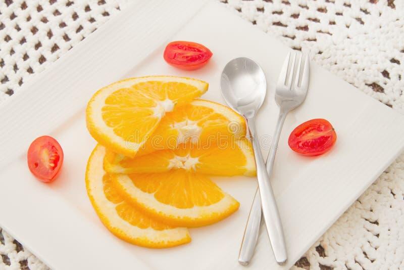 Naranjas cortadas con el tomate rojo fotografía de archivo