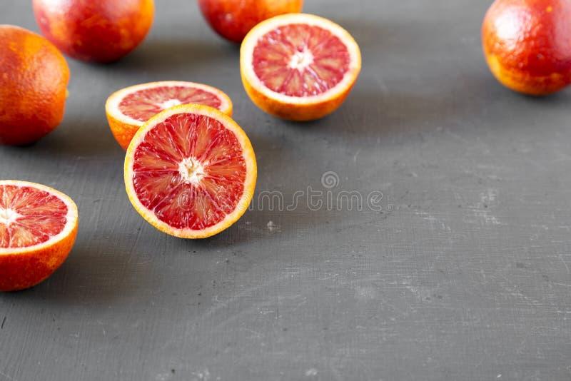 Naranjas de sangre enteras y partidas en dos en el fondo negro, opinión de ángulo bajo Copie el espacio imagen de archivo
