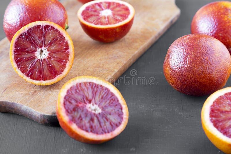Naranjas de sangre enteras y partidas en dos en el fondo negro, opinión de ángulo bajo primer foto de archivo libre de regalías