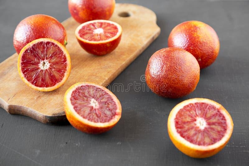 Naranjas de sangre enteras y partidas en dos en el fondo negro, opinión de ángulo bajo Primer imagenes de archivo