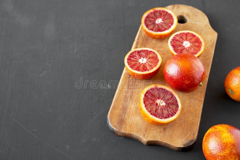 Naranjas de sangre enteras y partidas en dos en la superficie negra, opinión de ángulo bajo Copie el espacio fotografía de archivo