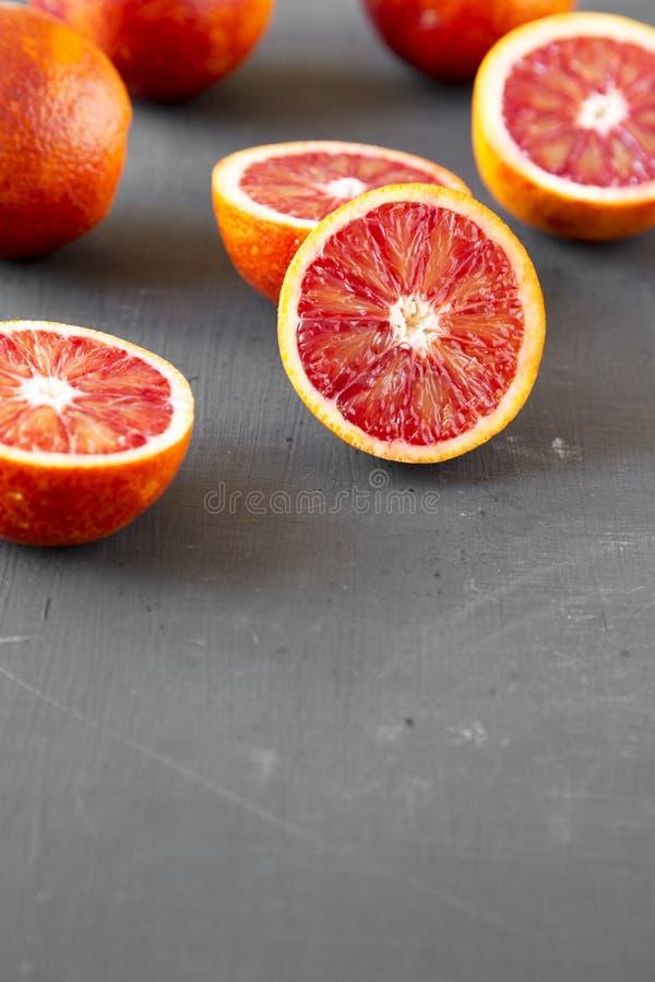 Naranjas de sangre enteras y partidas en dos en la superficie negra, opinión de ángulo bajo Copie el espacio foto de archivo libre de regalías