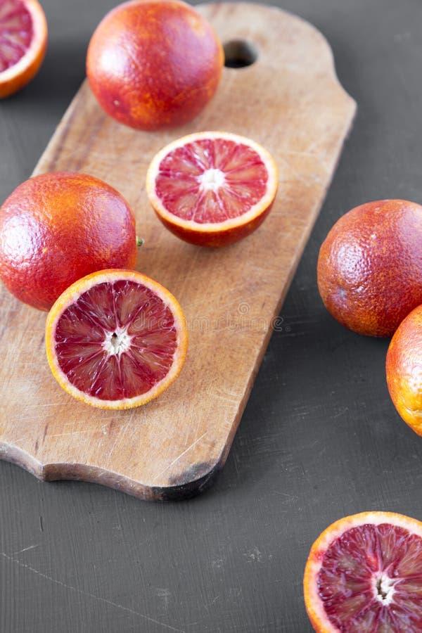 Naranjas de sangre enteras y partidas en dos en la superficie negra, opinión de ángulo bajo Primer imagenes de archivo