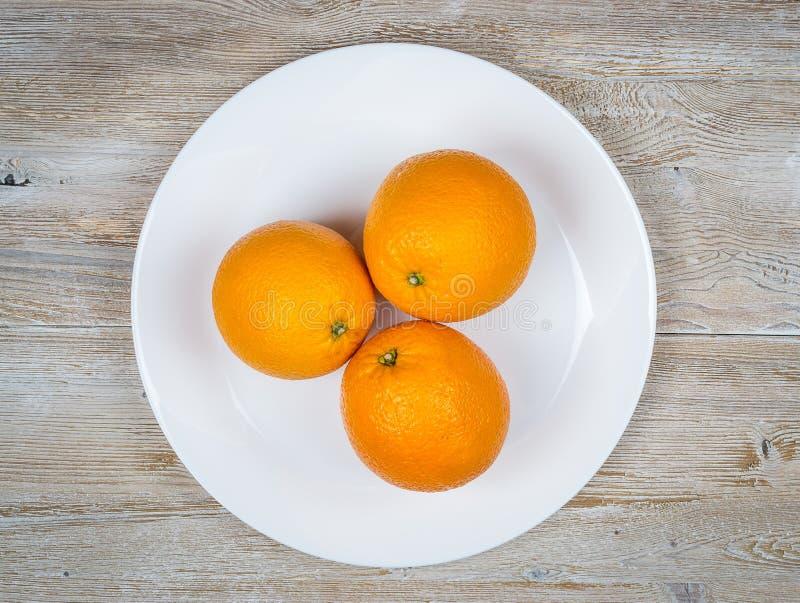 Naranjas frescas en una placa blanca en un primer de madera rústico de la tabla Visión superior foto de archivo libre de regalías