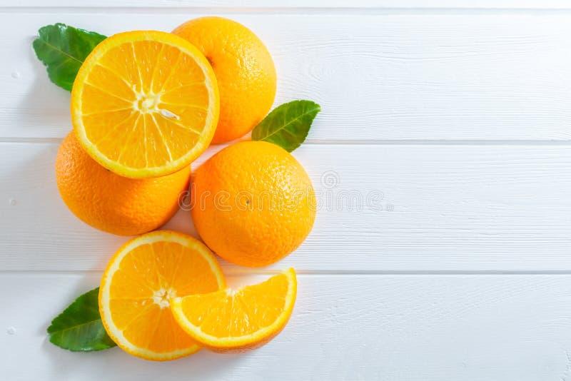 Naranjas frescas y hojas verdes en la tabla de madera blanca Plano-endecha, visi?n superior fotografía de archivo