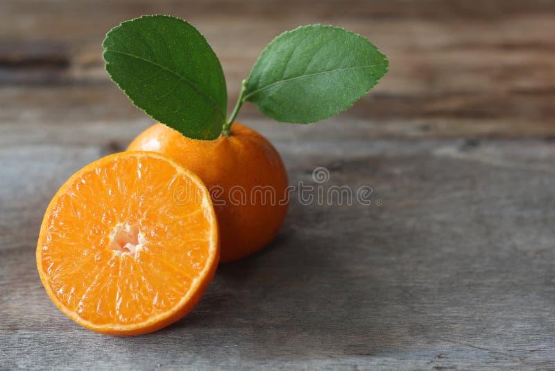 naranjas frescas y media en la tabla de madera imagen de archivo
