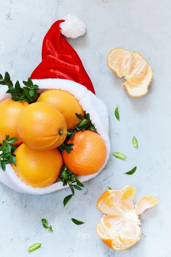 Naranjas maduras en el sombrero de Santa Claus con la planta del boj en un fondo azul Humor festivo imagen de archivo libre de regalías