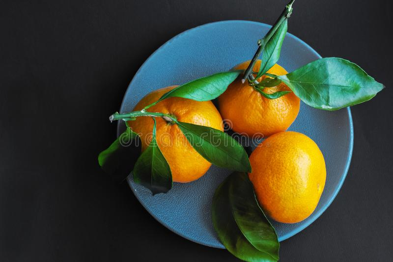 Naranjas maduras en una placa azul en un fondo negro fotos de archivo