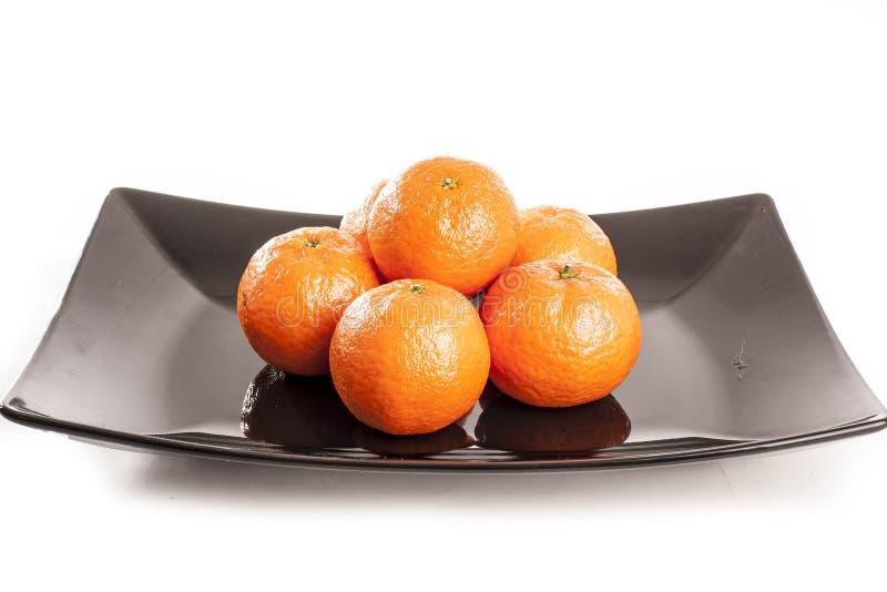 Naranjas, mandarina de las mandarinas de los mandarines, en fondo del estudio y la placa negra blancos aislados fotografía de archivo
