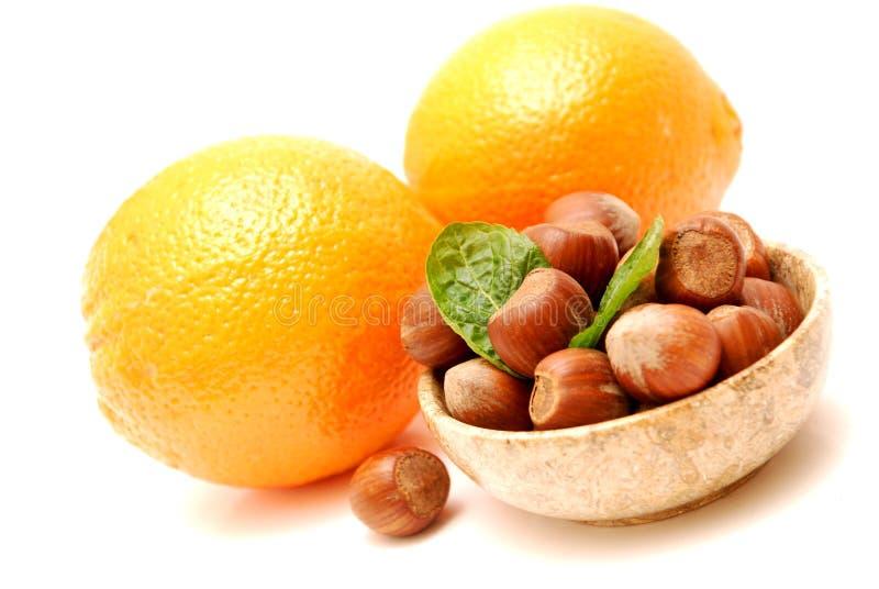 Naranjas y avellanas en un tazón de fuente de mármol imagen de archivo libre de regalías