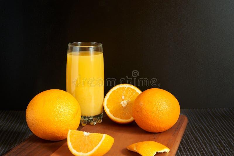 Naranjas y jugo en fondo negro foto de archivo libre de regalías
