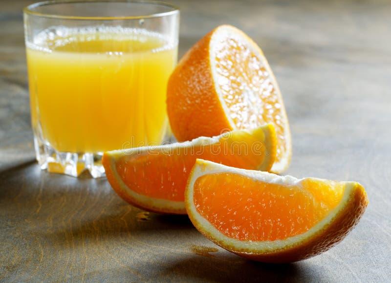 Naranjas y vidrio cortados de jugo foto de archivo