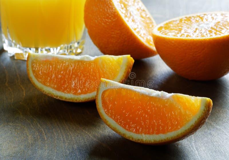 Naranjas y vidrio cortados de jugo imagen de archivo