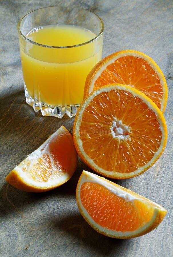 Naranjas y vidrio cortados de jugo fotos de archivo libres de regalías