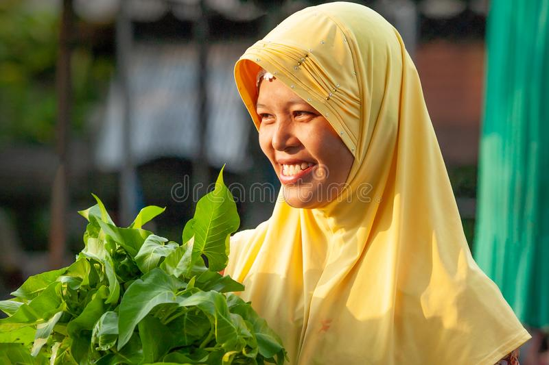 Portrait Thai-Muslim women in traditional clothing, hijab or niqab, holding vegetable and smiling in the daily morning market. Na stock photos