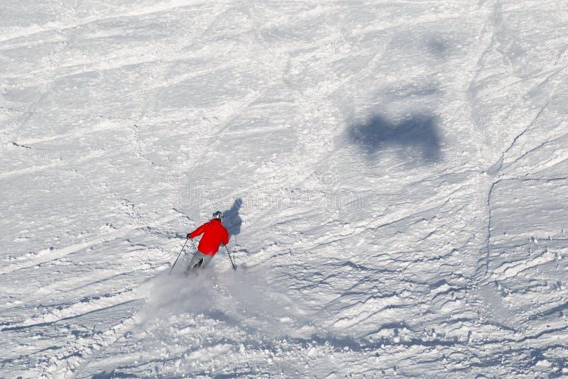 Narciarka jedzie wzdłuż zbocze góry na zima słonecznym dniu zdjęcia stock