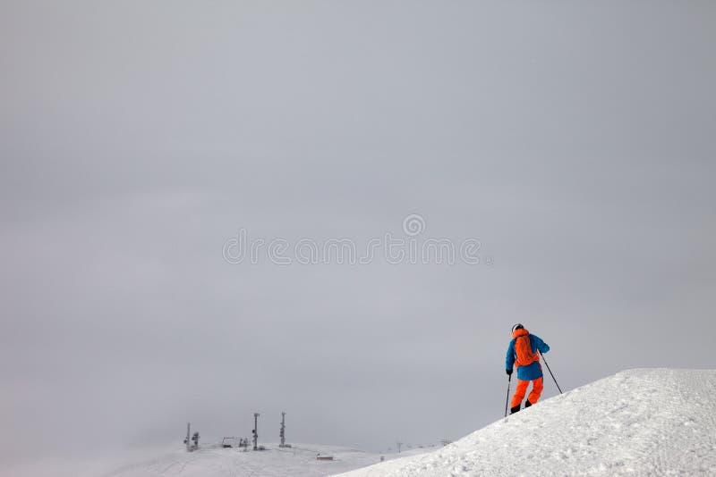 Narciarka przed zjazdowym na freeride skłonie i mglistym niebie obraz stock