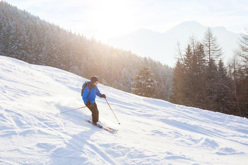 Narciarka w zmierzch górach, zjazdowy narciarstwo zdjęcie stock