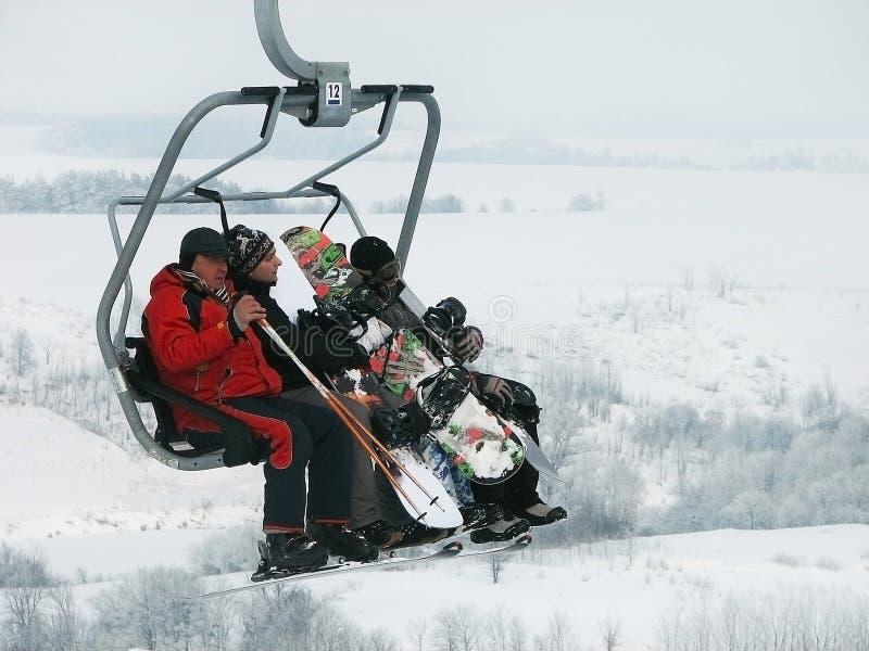 Narciarki i snowboarders są na narciarskim dźwignięciu (chairlift) zdjęcia stock
