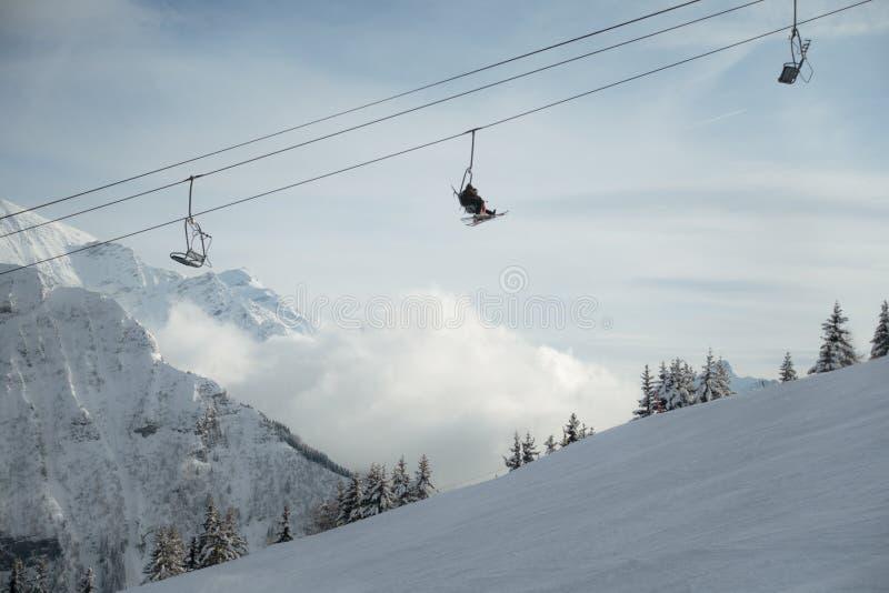 Narciarki w narciarskim dźwignięciu wysokim w śnieżnej chmurnej górze obraz royalty free
