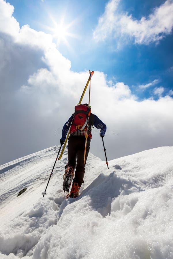 Narciarski alpinista chodzi up wzdłuż stromej śnieżnej grani z s zdjęcia royalty free