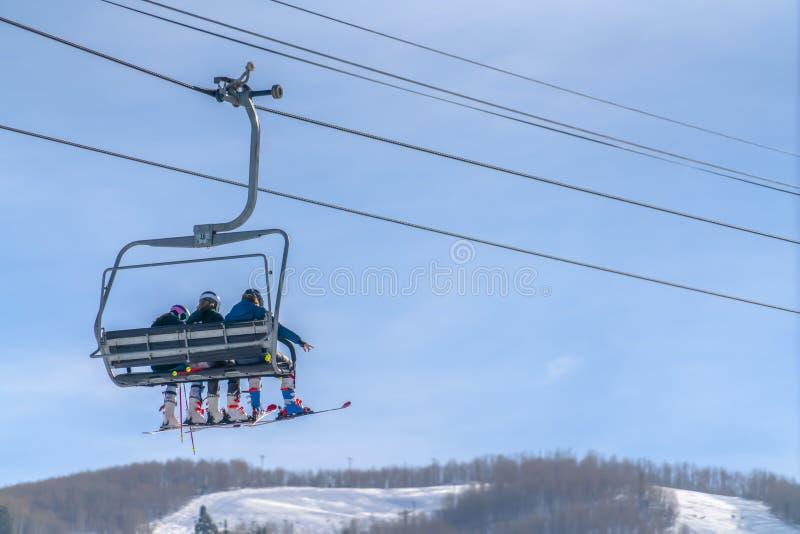 Narciarski dźwignięcie z narciarkami przegapia niebo i górę zdjęcie stock