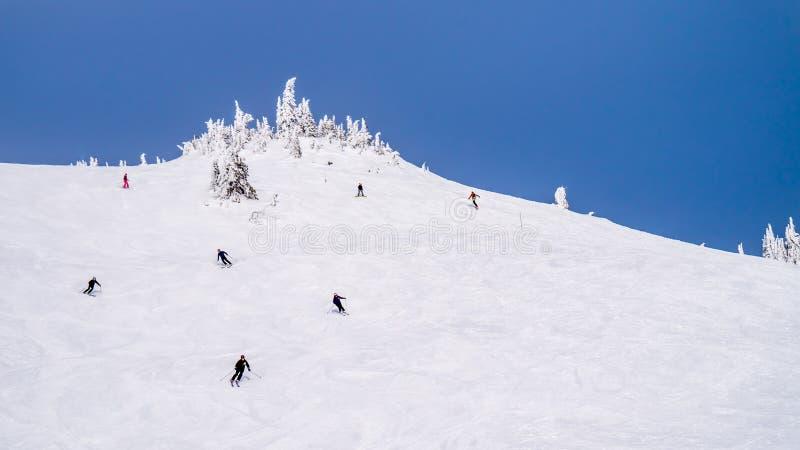 Narciarstwo na wysokich wysokogórskich skłonach Narciarscy wzgórza przy Alpejską wioską słońce Osiąga szczyt zdjęcie stock
