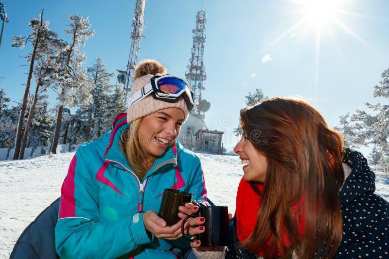 Narciarstwo, zimy zabawa - przyjaciele cieszy się na gorącym napoju przy ośrodkiem narciarskim zdjęcie stock