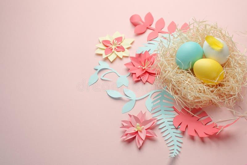 Narcisos da cor de papel do origâmi, ovos no ninho no fundo da cor, cartão do éster, flor de papel do origâmi, cópia imagem de stock