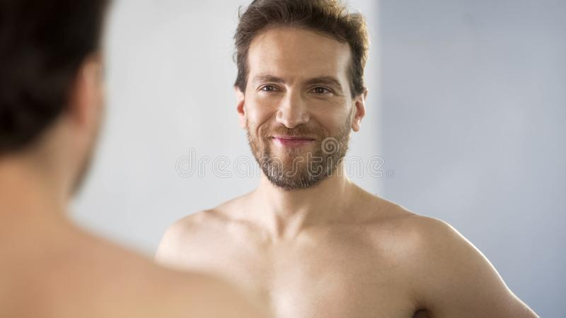 Narcissistic middle-aged man admiringly looking at his reflection in mirror stock images