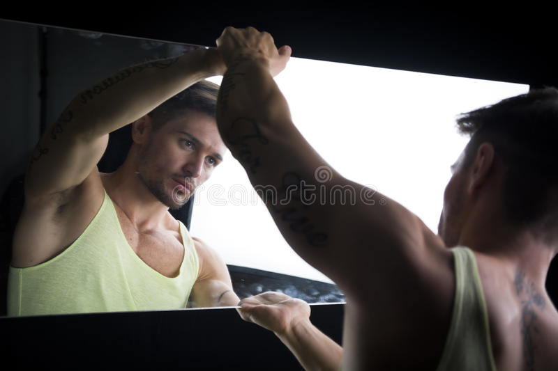 Narcissistic young man admiring his reflection. Narcissistic handsome young man leaning forwards admiring his reflection in the mirror in a show of self royalty free stock image